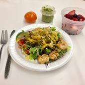 Shrimp fajitas over a salad dressed with a wedge of lime, guacamole on the side and some fruit