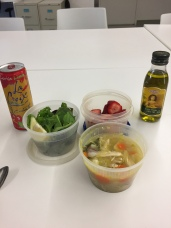 a small salad, sliced strawberries, chicken soup, sparkling water