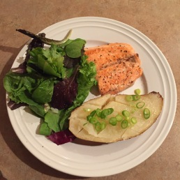 Salmon, half of a baked potato, salad