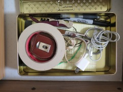 I use an old cookie tin to hold kitchen utilities